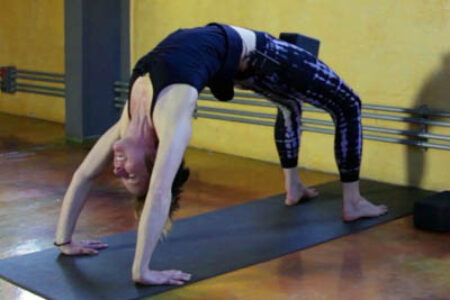Tiffany Wood practices Urdhva Dhanurasana (wheel yoga pose) using a block between her legs